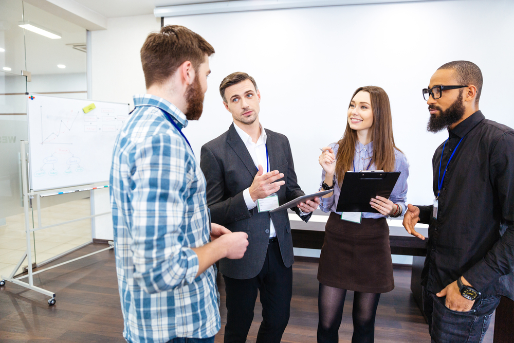 Head of department standing and talking to smiling young employees in office